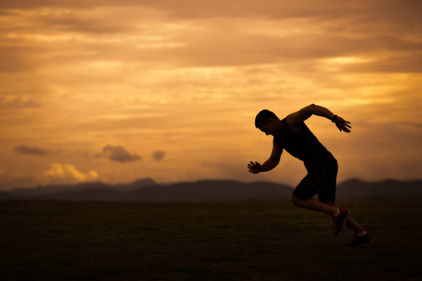 asian men are siluate jogging at a speed in the evening - carpet runner stock photos and pictures