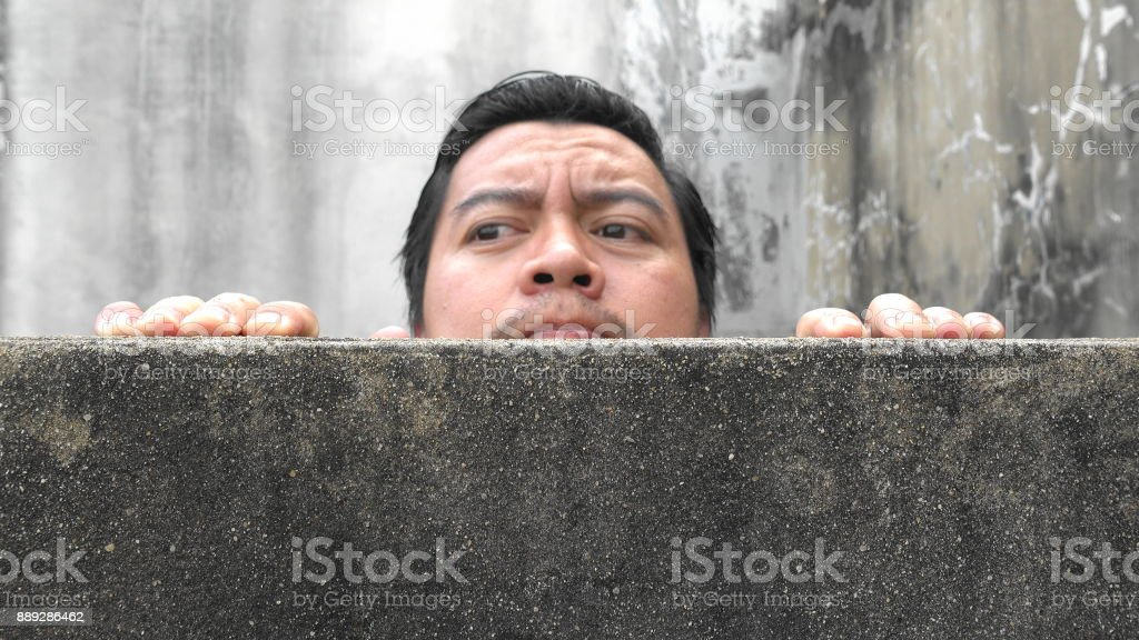 Asian men climb up concrete walls appearing suspiciously stock photo
