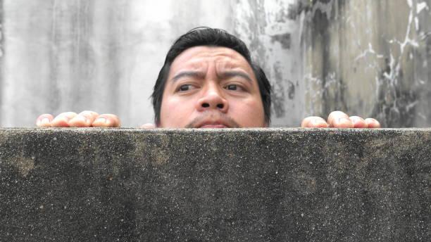asiatische männer hochklettern betonwände, die verdächtig erscheinen - peeping tom stock-fotos und bilder
