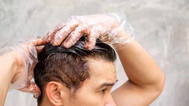 aziatische mannen kleurstof zijn haarkleur op een grijze achtergrond. - gekleurd haar stockfoto's en -beelden