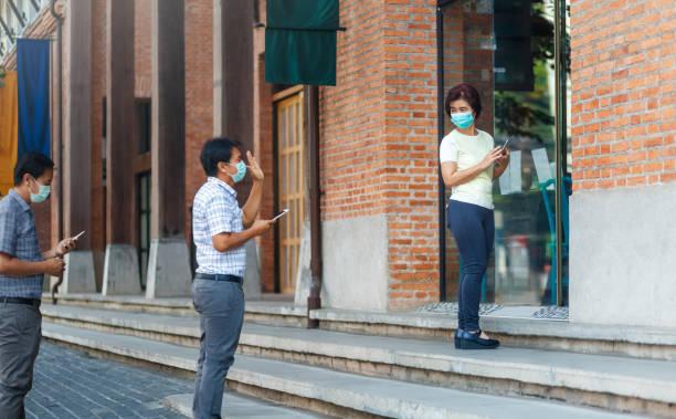 Las personas de mediana edad asiáticas que usan máscara y mantienen el distanciamiento social para evitar la propagación de COVID-19 - foto de stock