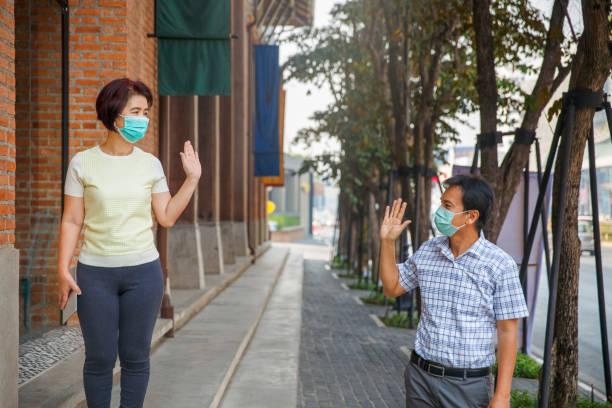Asiatische Menschen mittleren Alters tragen Maske und halten soziale Entsung, um die Ausbreitung von COVID-19 zu vermeiden – Foto