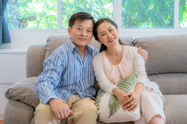 Asian middle-aged couples sit and relax on the sofa in the living room. stock photo
