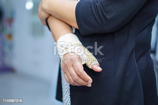 Asian middle-aged lady woman use elastic bandage to treating De Quervain syndrome at hand and finger in office.