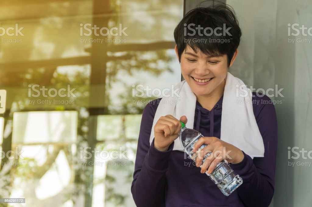 Asian Middle-aged woman holding a bottle of water after exercise. royalty-free stock photo