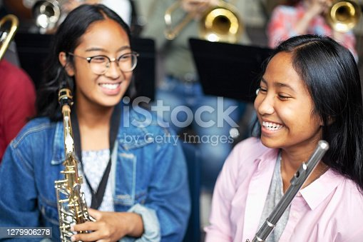 Confident Asian mixed race teenage girls playing brass instruments in classroom. Students are practicing music at high school. They are learning musical instruments.