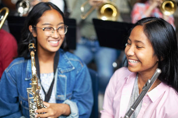 Asian mixed race teenage female music students talking and laughing with brass instruments in class stock photo