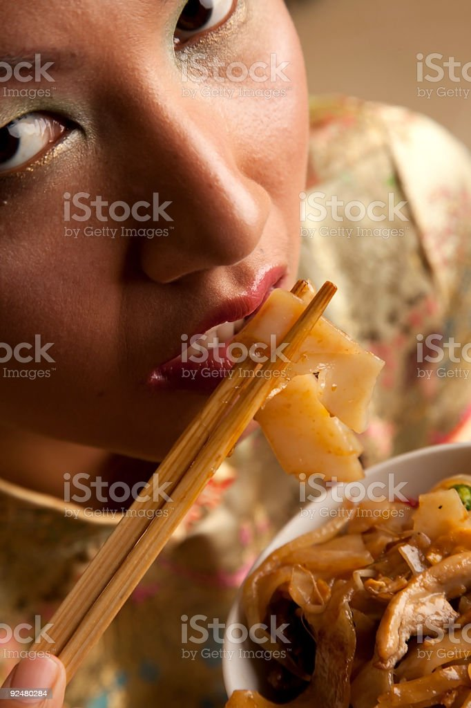 Asian model eating noodles in traditional dress royalty-free stock photo