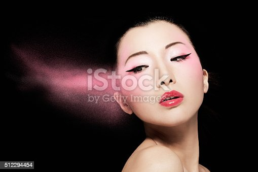 istock Asian model with pink powder isolated on black. 512294454