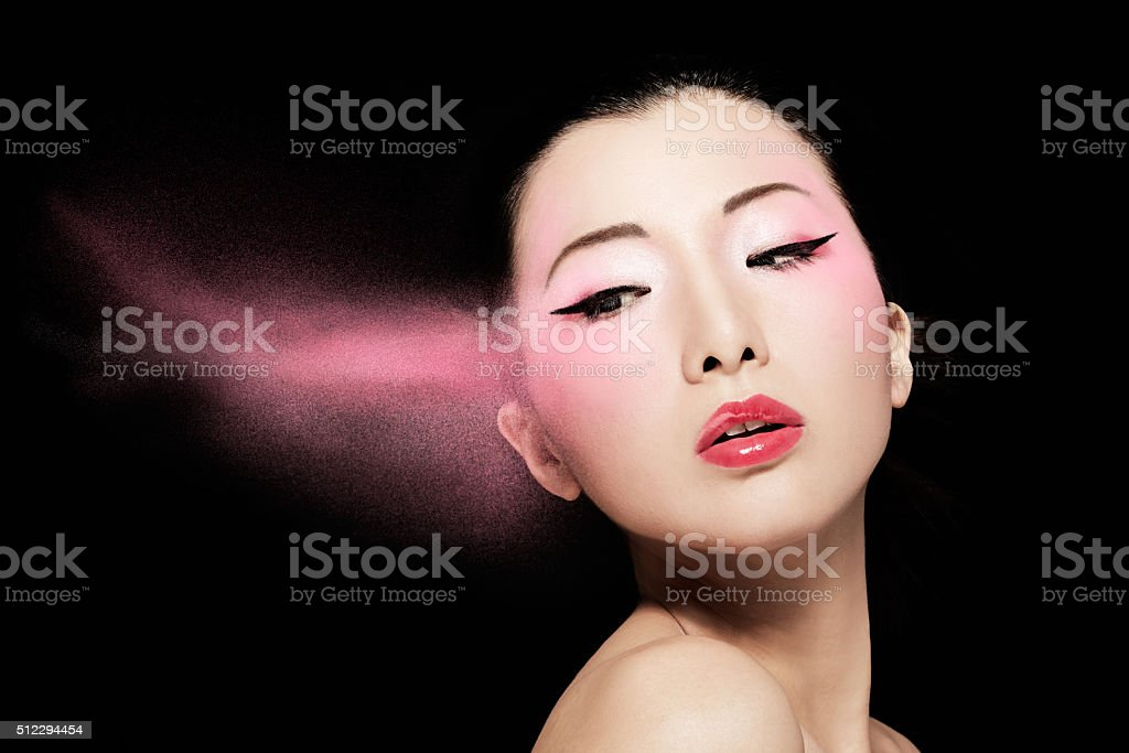 Asian model with pink powder isolated on black. stock photo