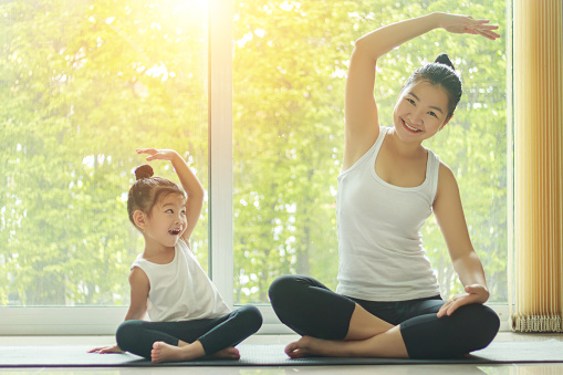 Asian mom practice yoga at home with a adorable daughter sitting next to her, trying to imitate the mother's posture with a smiling face while exercise at home.