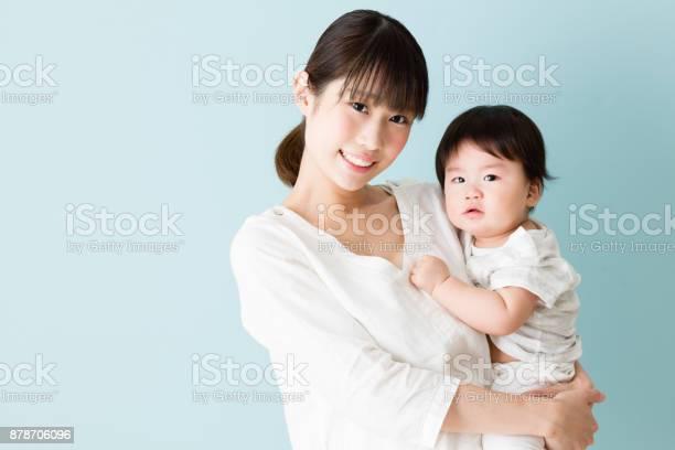 アジアの母と赤ちゃんの青い背景に分離 - 2人のストックフォトや画像を多数ご用意