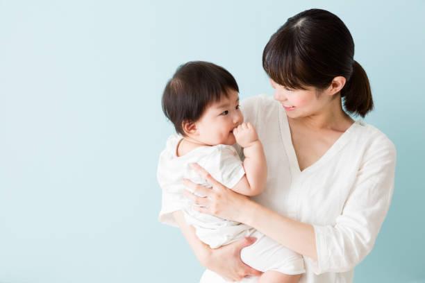 アジアの母と赤ちゃんの青い背景に分離 - スタジオ 日本人 ストックフォトと画像