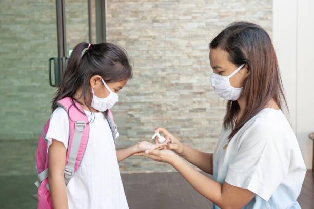 Asiatische Mutter und Kind Mädchen tragen Schutzmaske mit Desinfektionsmittel Gel waschen Hand, um Kontamination durch Viren und Bakterien vor und nach draußen zu verhindern Coronavirus covid19 Ausbruch zu stoppen. – Foto