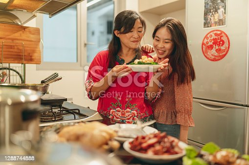 Asian mother and daughter bonding during food preparation for Chinese New Year's eve reunion dinner