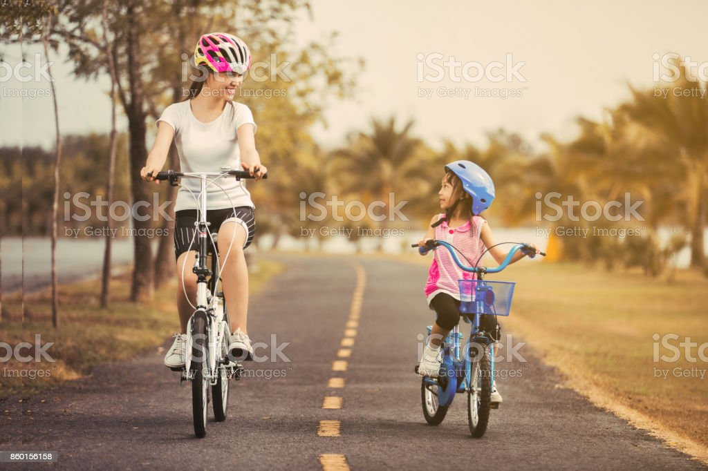 Asian mother and daughter cyclist in the park. stock photo