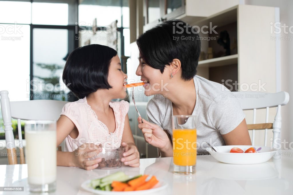 Asian mother and daughter eating in the kitchen. stock photo