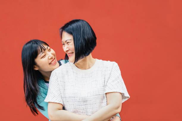 アジアの母と娘抱擁屋外-幸せな中国の家族の時間を一緒に楽しみます-親、愛と人々のライフスタイルコンセプト - 母娘 笑顔 日本人 ストックフォトと画像
