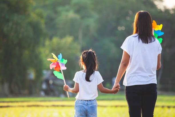 Asiatische Mutter und Tochter halten Hand und spielen mit Windkraftanlage Spielzeug zusammen im Reisfeld – Foto