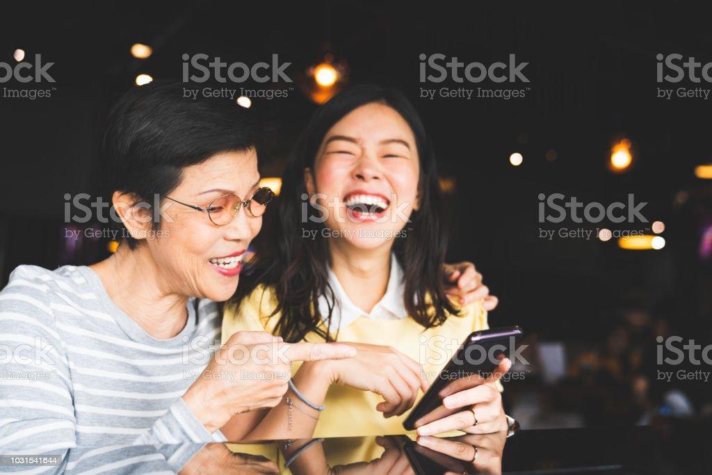Asia madre e hija riendo y sonriendo en un álbum de foto o selfie, utilizando smartphone juntos en el restaurante o cafetería, con copian espacio. Amor familiar, la actividad de vacaciones o concepto de estilo de vida moderno foto de stock libre de derechos