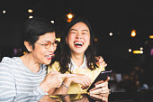 Asian mother and daughter laughing and smiling on a selfie or photo album, using smartphone together at restaurant or cafe, with copy space. Family love, holiday activity, or modern lifestyle concept