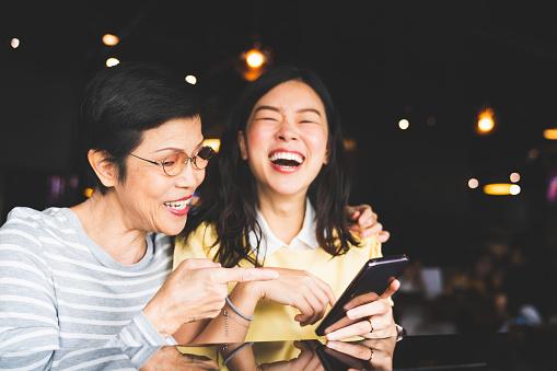 Asia Madre E Hija Riendo Y Sonriendo En Un Álbum De Foto O Selfie Utilizando Smartphone Juntos En El Restaurante O Cafetería Con Copian Espacio Amor Familiar La Actividad De Vacaciones O Concepto De Estilo De Vida Moderno Foto de stock y más banco de imágenes de Adulto