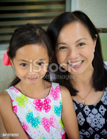 Vietnamese mother and daughter smile at camera