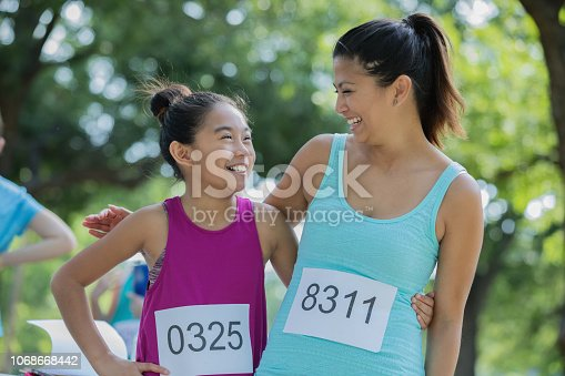 Asian mother and daughter pose together during a marathon.  The are in a public park on a sunny day.