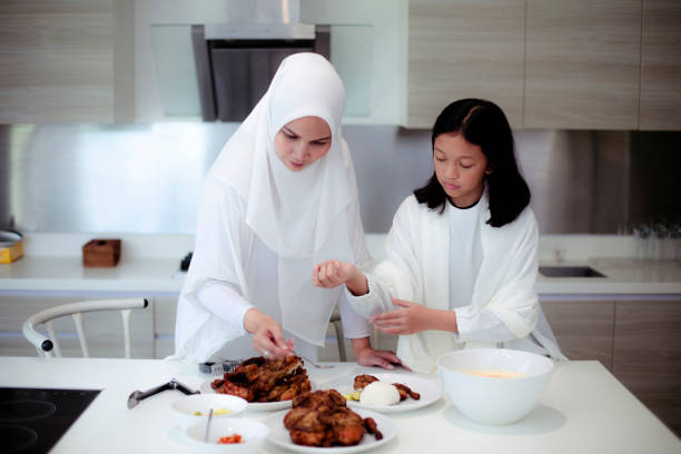asian mother and daughter preparing food in kitchen for fasting ramadhan stock photo