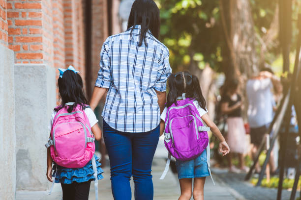 Asiatische Mutter und Tochter Schüler Mädchen mit Rucksack halten Hand und gehen zur Schule zusammen – Foto