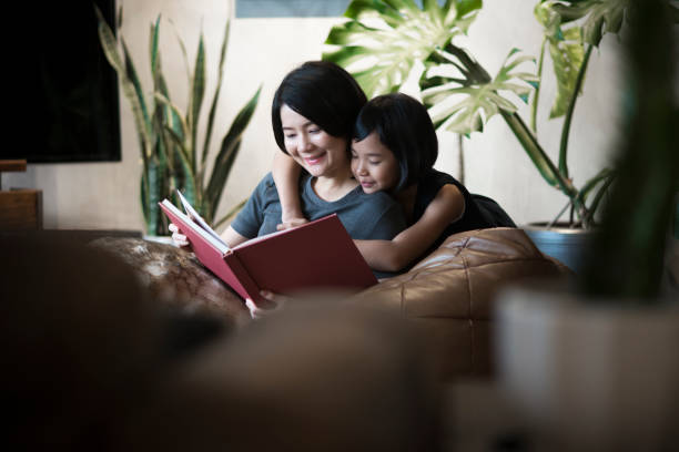 asiatische mutter und tochter zu hause ein buch zu lesen. - kurzgeschichten stock-fotos und bilder
