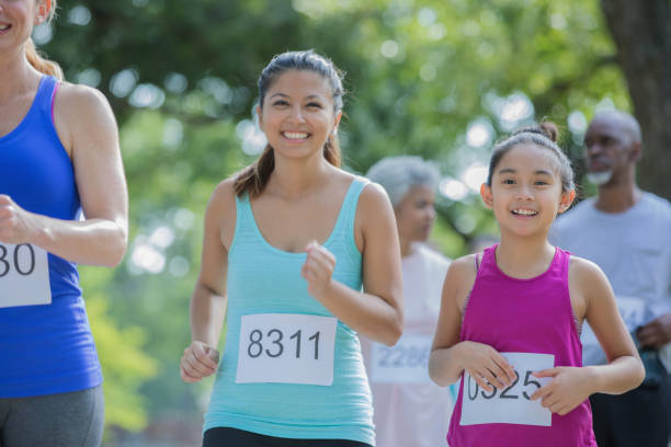 Asian mother and daughter run together in a marathon stock photo