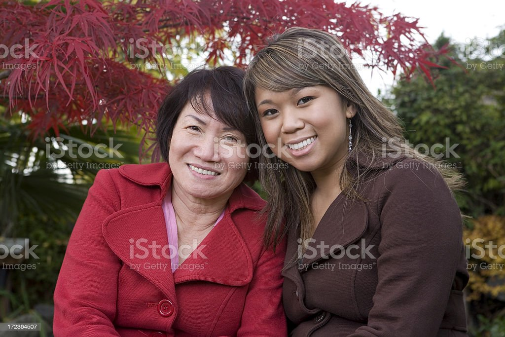 Asian Mother and Daughter Smiling in Outdoor Fall Portrait royalty-free stock photo