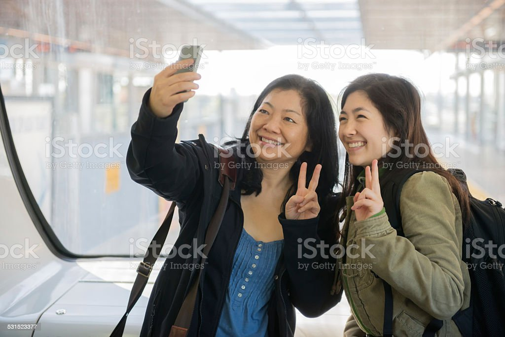 Asian Mother and Daughter Taking Selfie on Train stock photo