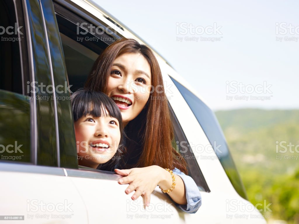 asian mother and daughter traveling by car stock photo