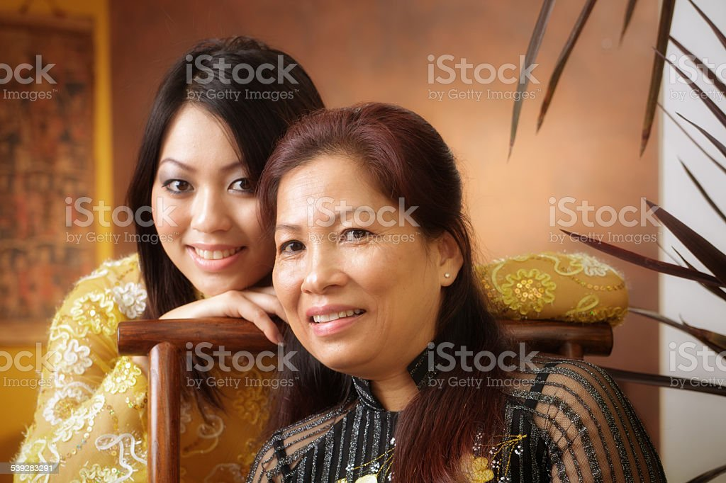 Asian Mother and Daughter, Vietnamese Family Smiling Lovingly at Home stock photo