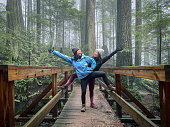 istock Asian Mother and Eurasian Daughter Posing on Bridge in Forest 1293847786
