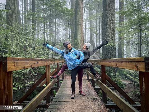 Mature mother and young adult daughter enjoying winter walk through wet forest on Mount Seymour, North Vancouver, British Columbia, Canada