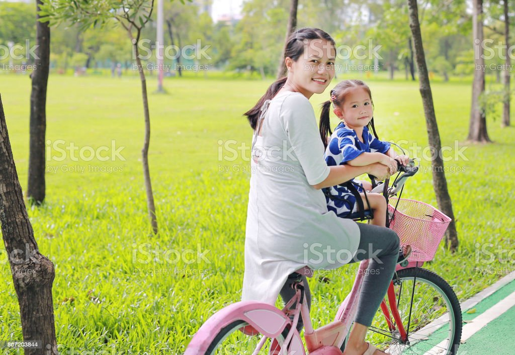Asian mother and her child girl on a bike at the park in the morning. stock photo