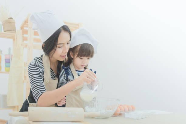 Asiatische Mutter und ihre Tochter den Teig vorbereiten, um einen Kuchen zu backen. – Foto