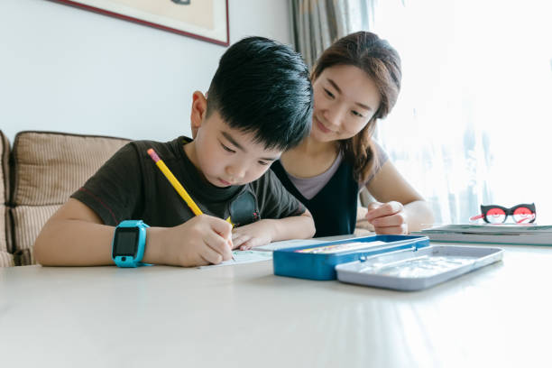 Asian mother and son doing homework. stock photo