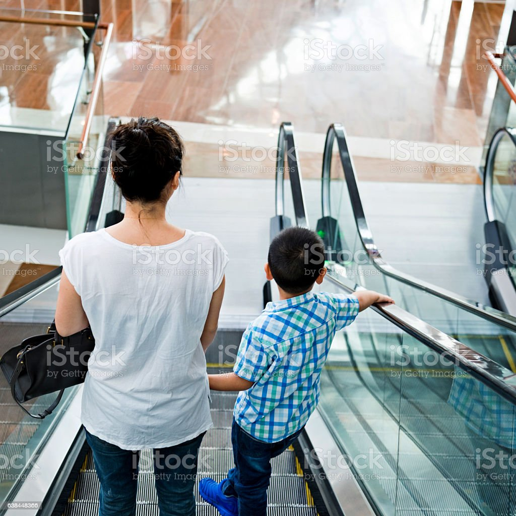Asian mother and son on escalator stock photo