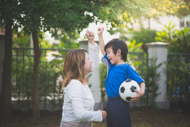 Asian mother and son Playing Soccer stock photo