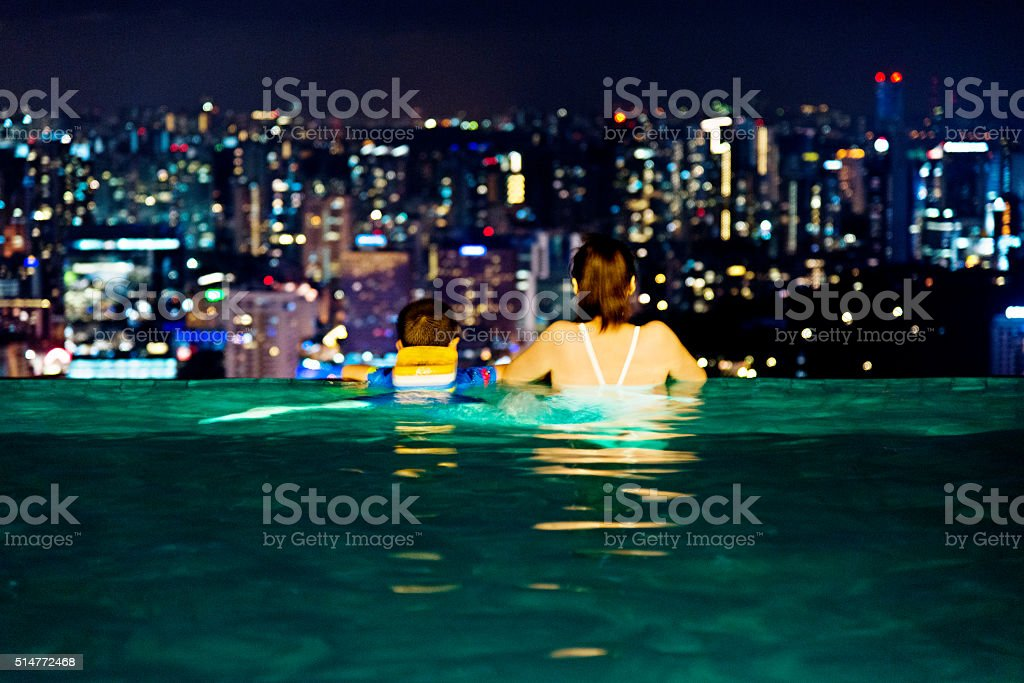 Asian mother and son relaxing on hotel rooftop stock photo