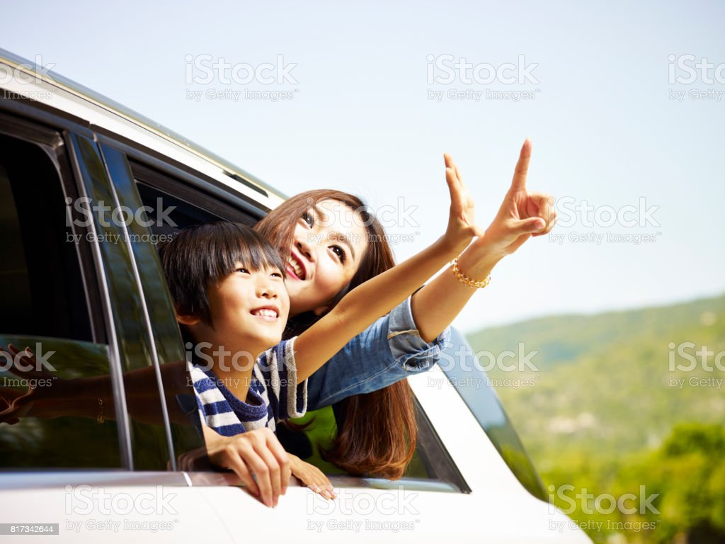 asian mother and son traveling by car stock photo