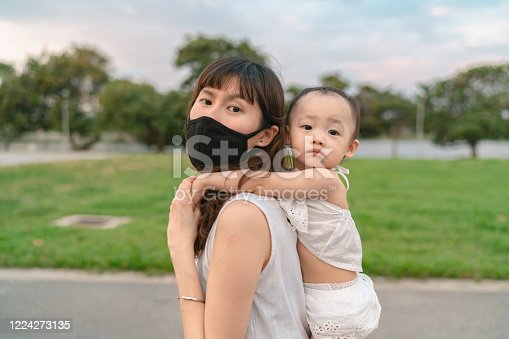 Asian mother caring for her child while exploring outdoors in corona virus pandemic