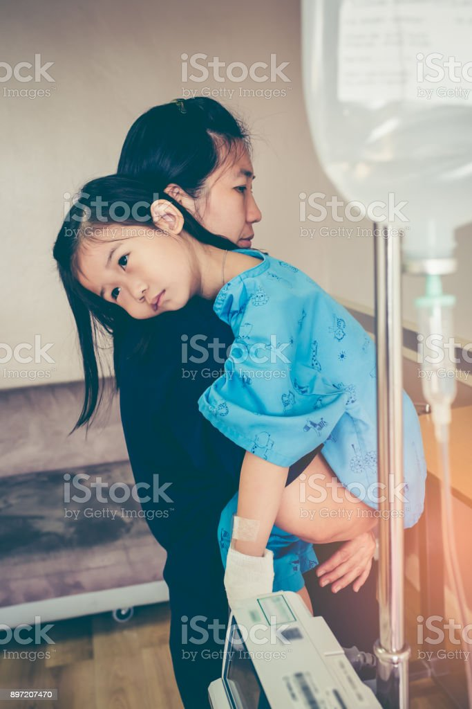 Asian mother carrying her daughter, saline IV drip on child's hand. stock photo