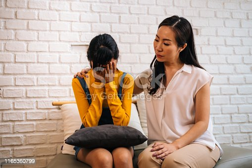 Asian mother comforting crying teenage daughter in miserable, stressed, depressed, sad state of mind. 40s Mom is putting hands over this adolescent teenager shoulders at indoors room.