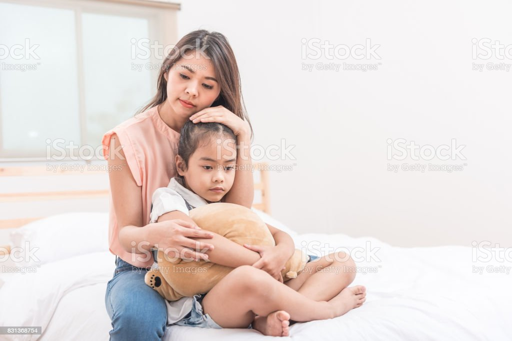 Asian mother comforting her sad daughter stock photo