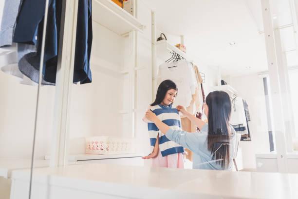 asiatische mutter dressing/auswahl kleider zu ihrer mädchen tochter aus schrank im schlafzimmer, asiatische familie lifestyle konzept - mutterkleiderschrank stock-fotos und bilder